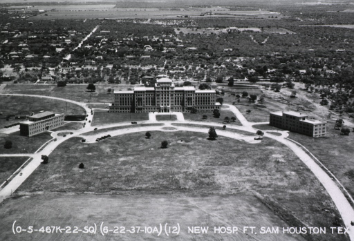 <p>Aerial photograph of the front of the new hospital at Fort Sam Houston in Texas. The main building stands at the apex of a circular drive; on either side of the main building, two smaller buildings stand equidistant.</p>