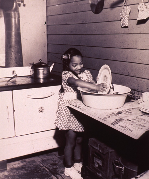 <p>A young girl is washing the dishes in a tub placed on newspapers on a table.</p>