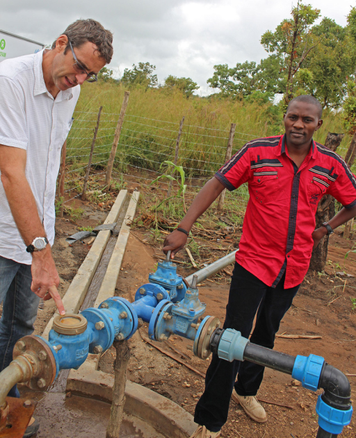 Oxfam staff members Tim Sutton (left) and Pius Nzuki Kitonyi (right) with the soon-to-be-repaired water pump in Adjumani. In disaster-affected situations, Oxfam takes a lead in delivering WASH-related services.© Wendee Nicole
