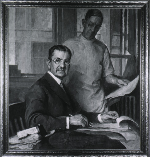 <p>Seated at table, full face, holding paper and pencil.</p>