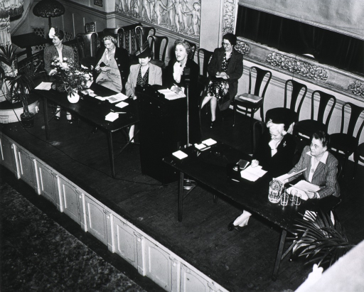 <p>View of board members on stage during a meeting giving presentations.  General members of the organization are not shown.</p>