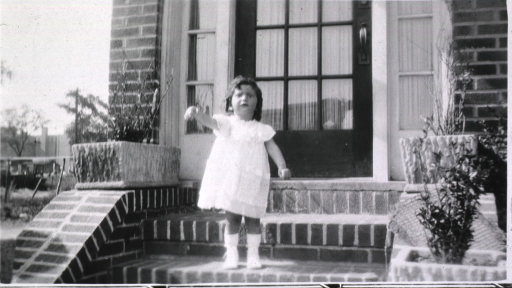 <p>Showing little girl standing on steps waving good bye.</p>