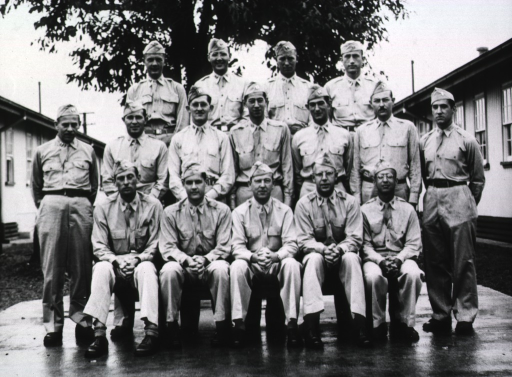 <p>Sixteen military personnel, all male, pose in three rows in front of a single-floor, U-shaped building.  The base and servicemen are not identified.  (This is one of a series of photographs taken of servicemen in the same place and are housed in the same box (no. 45, no. 47, and no. 48).)</p>