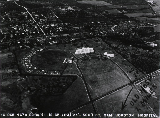 <p>Aerial photograph of the hospital at Fort Sam Houston in Texas.  The main building stands at the apex of a circular drive; on either side of the main building, two smaller buildings stand equidistant.  Other smaller buildings in the complex are situated along another circular road adjacent to the the drive on which the main building sits.  The photograph is marked in red crayon, with a lines drawn to show the limits of the hospital grounds.  Some of the buildings are marked with acronyms, and an arrow at the bottom of the print points in the direction of the previous hospital (&quot;Old Hosp 2 Miles&quot;).</p>