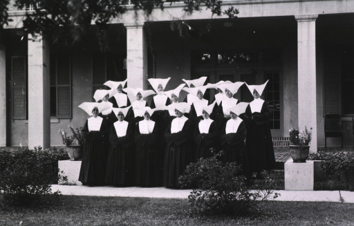 <p>Exterior view: a group of nuns stand on the steps of a building at the U.S.P.H.S. hospital at Carville, La.</p>