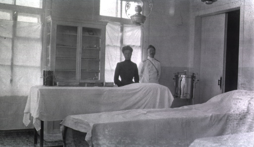 <p>A nurse and physician stand in the operating room at Military Hospital No. 3.</p>