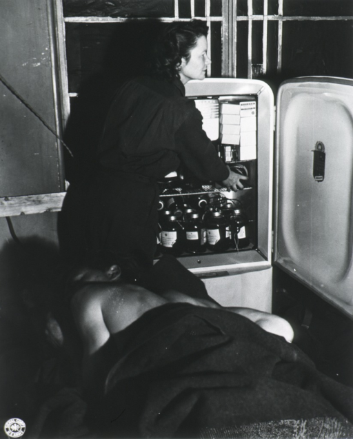 <p>Standing, profile; reaching into ice box for blood plasma for patient.</p>