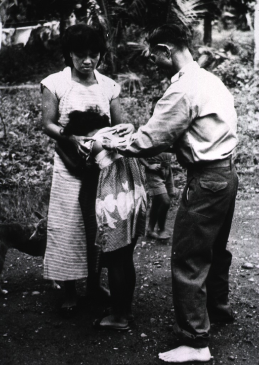 <p>A barefooted man is giving a young girl an injection on her back; it is her 15th daily injection after having been licked on an open cut by a dog.</p>