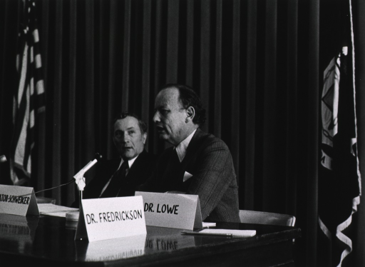 <p>Dr. Donald S. Fredrickson, director of the National Institutes of Health (NIH), is seated at a table with Richard S. Schweiker, the Republican Pennsylvania senator.  There are two microphones on the table.  Also on the table are the names of Senator Schweiker, Dr. Fredrickson, and Dr. Lowe on name tents.  Dr. Lowe's name tent is in front of Dr. Fredrickson.  The U.S. flag is at one end of the table; another flag is behind Dr. Fredrickson.</p>