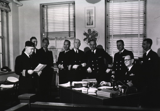 <p>Interior view: a group of men wearing PHS uniforms gathered together in an office; Dr. Johansen is seated at his desk.</p>