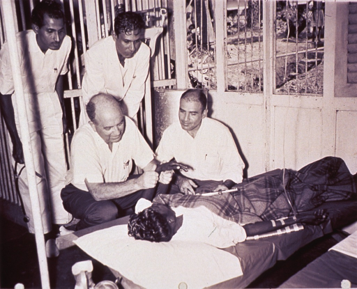 <p>Public Health Service physicians, Dr. Alexander Langmuir (kneeling left) and Dr. Robert Oseasohn (kneeling right) and two Pakistani doctors examine cholera patient in the barge hospital at Matlab Bazer, East Pakistan.</p>