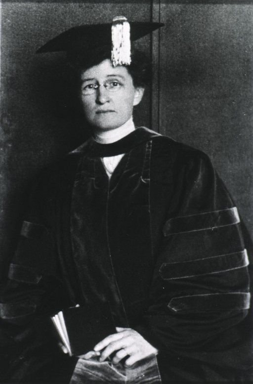 <p>Three quarter length, full face; wearing glasses; in academic robes, holding diploma.</p>