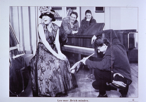<p>Predominantly white poster with black lettering.  Poster dominated by a b&amp;w photo reproduction featuring four young adults gathered around a piano and laughing.  The woman on the piano bench wears a somewhat elaborate dress and hat.  A man is on his knees in front of her.  He holds a tulip, as if he were offering it to the woman.  Another man and woman look on from behind the piano.  Title below photo.  Publisher information in lower right corner.</p>
