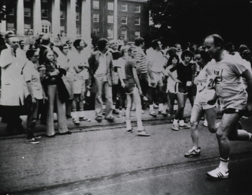 <p>Dr. Donald S. Fredrickson, director of the National Institutes of Health (NIH), participates in running relay with his team, Donald's Ducks, who finish out of the money.  The road he is running on is lined with people.  They are running past a three-storied columned building.</p>