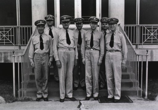 <p>Group portrait of seven men (full-length portrait, standing) in Public Health Service uniforms on the steps of a building at the Public Health Service Hospital, Carville, La.</p>