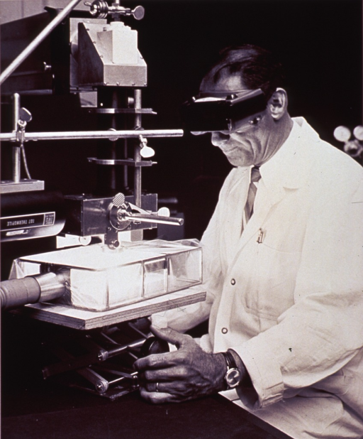 <p>A man in a white lab coat is sitting in front of a laser device, turning a knob.  He is wearing eye protection.  One of the parts of the machine is labelled &quot;107 Thermopile.&quot;</p>