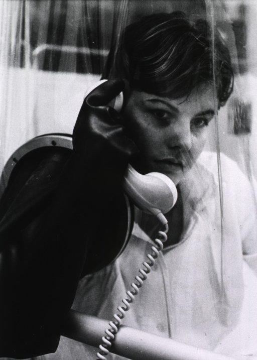 <p>Interior view: a young bone marrow transplant patient is talking on the telephone; she is in a specially designed aseptic room with hand-ports through which she is able to manipulate the telephone.</p>