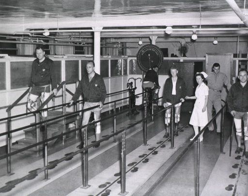 <p>Four men with prosthetic legs walk on an indoor track equipped with hand rails.  One of the tracks has a set of stairs.  The floor is marked with a course of footprints that are meant to be stepped on in sequence as part of the rehabilitation.  A nurse and another staff member are present on the track.  In the background a man exercises on a stationary bike.</p>