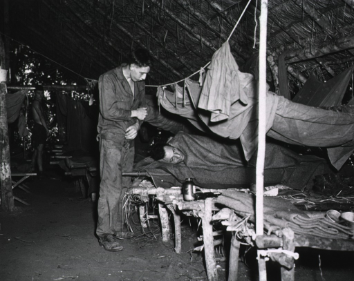 <p>A row of makeshift cots lines one side of a hospital tent.  One serviceman stands above another who lies under a blanket on the cot.  In the background a shirtless serviceman stands and watches.</p>