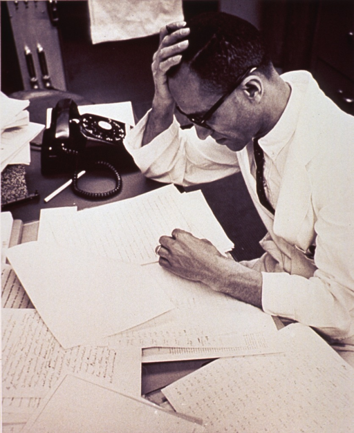 <p>A man, sitting at a desk, is proofreading typewritten pages.</p>
