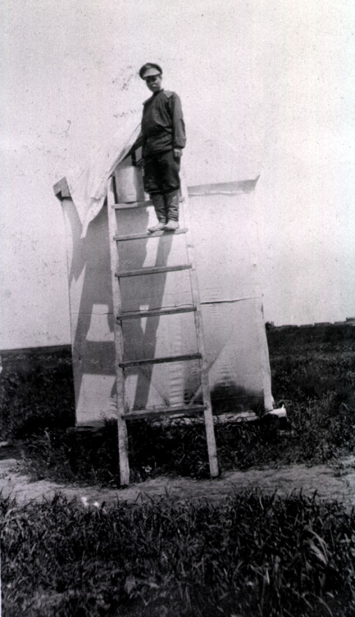 <p>A soldier holding a bucket stands on a ladder leaning against a tent enclosure that serves as a bath house.</p>