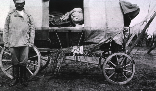 <p>A soldier stands beside a wagon filled with field hospital material.</p>