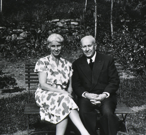 <p>Three quarter length, seated on bench in garden with his wife &quot;Emmy&quot;.</p>
