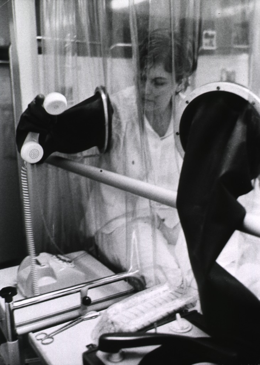 <p>Interior view: a young woman, recent recipient of a bone marrow transplant, is using a telephone through a hand-port in a specially designed aseptic room.</p>