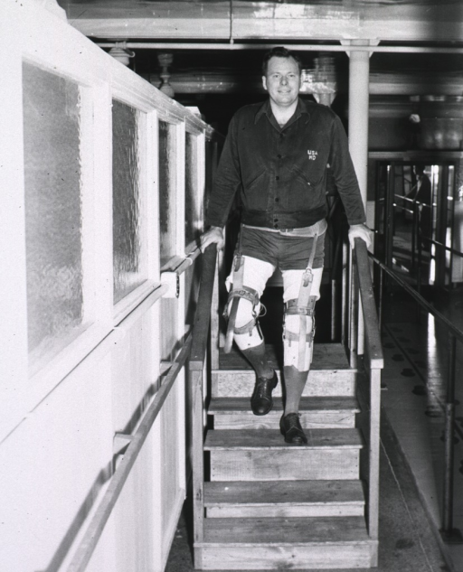 <p>A man with two prosthetic legs holds onto the railing as he proceeds to walk down a set of steps that is part of a indoor track in a rehabilitation center.  This man is the same man photographed in the same setting with four other amputees in another photograph (Prosthesis no. 2 box 1 mil).</p>