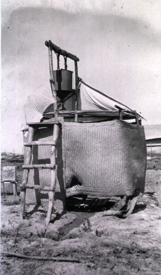 <p>An improvised bath house enclosed with a straw mat.  A bucket hangs over the enclosure while a ladder leans on it.</p>