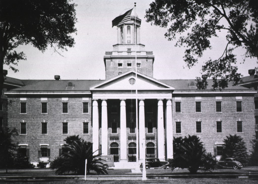 <p>Exterior view: front facade of the hospital building; vintage automobiles parked in front; forty-eight star flag on the flag pole.</p>