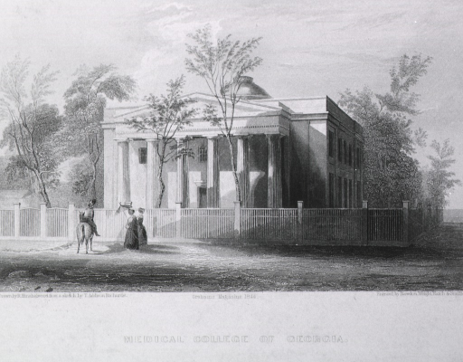 <p>Exterior view: a square building with portico and columns surrounded by a white fence. Two women are strolling by and a man on horseback has stopped in front of the building.</p>
