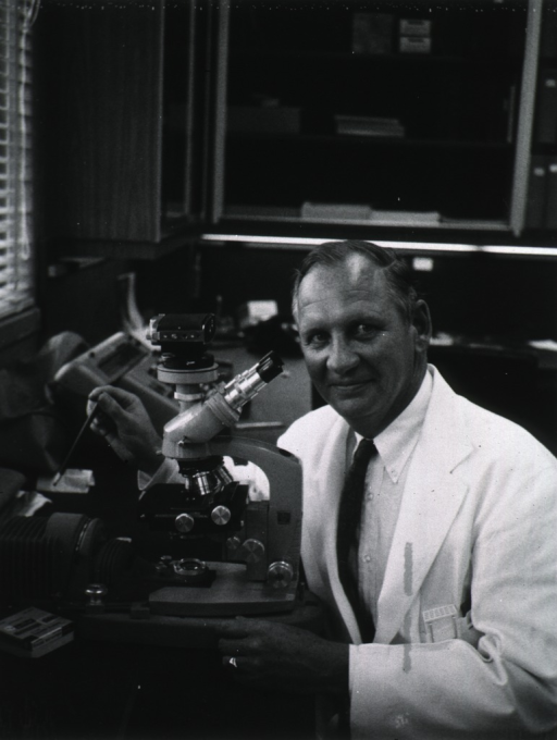<p>Half-length, full face, wearing lab coat, seated in lab at microscope.</p>