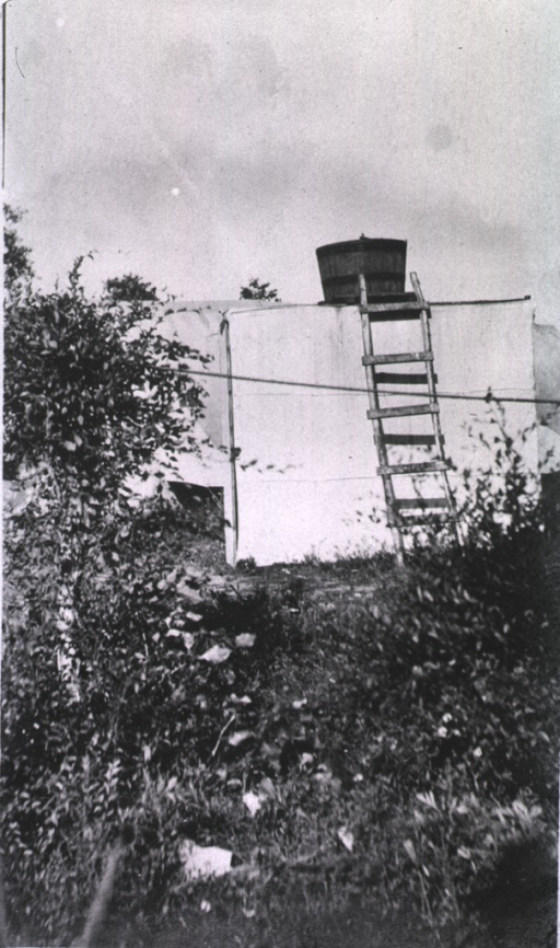 <p>A view of a bath house.  A ladder is resting against it while a bucket sits on top.</p>