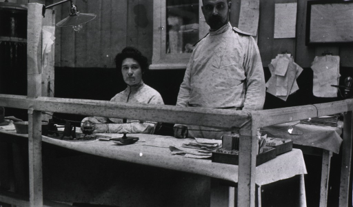 <p>Two staff people, a woman and a man, at a desk in the office of the Evacuation Commission.</p>