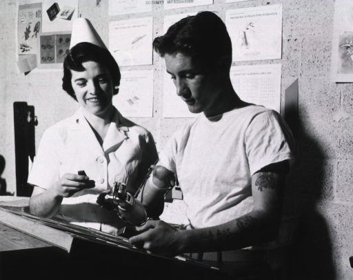 <p>A man with a prosthetic right arm stands next to the female therapist who assists the man in performing a task at work.  They both stand before a desk.  Behind them on the wall hang diagrams on the correct way to set type.</p>