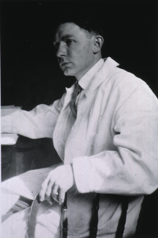 <p>Three-quarter length, left pose, seated, wearing white coat.</p>