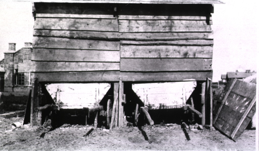 <p>The view from the back of a hospital latrine with wooden carts placed underneath.</p>
