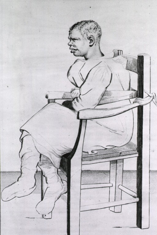 <p>A black man is sitting in a chair, he is wearing a gown (straitjacket) with the end of each sleeve tied to the opposite side of the chair.</p>