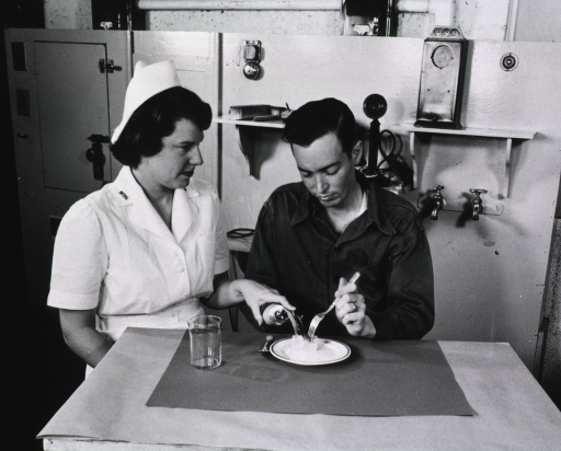 <p>A male amputee sits at a table next to a female therapist.  With the assistance of the therapist, the man cuts food on a plate.</p>