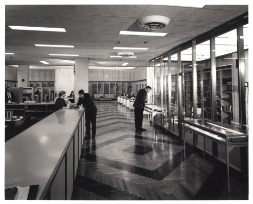 <p>The gleaming new reading room of the History of Medicine Division, NIH, Bethesda campus beckons from the entrance near the service desk. Division Chief John B. Blake leans over the desk and speaks with a librarian.</p>
