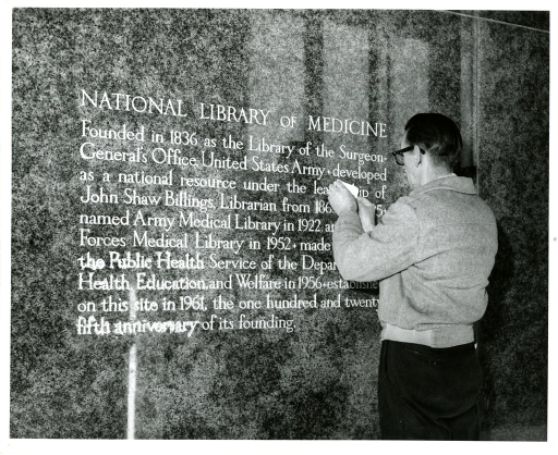 <p>A workman completes the gold leaf work on the inscription inside the entrance to the National Library of Medicine. The inscription describes the Library's history.</p>