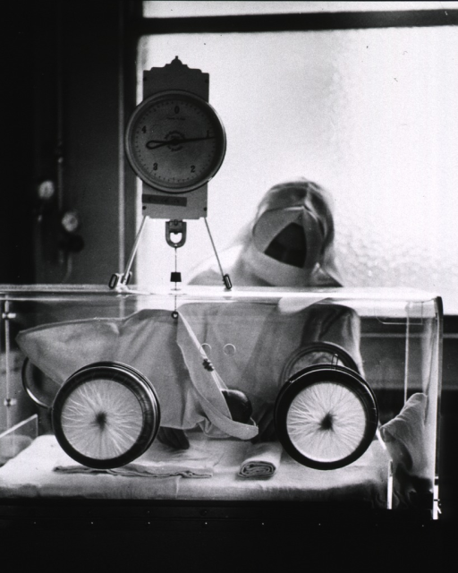 <p>Interior view: a nurse is weighing a premature infant in an incubator with hand-ports.</p>