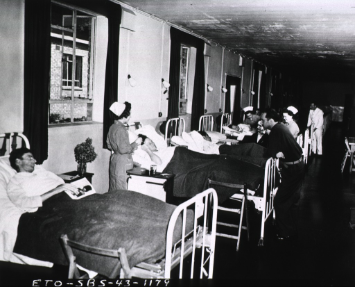 <p>Patients lie on hospital beds that line the wall of a surgical ward.  Nurses tend to the patients.</p>