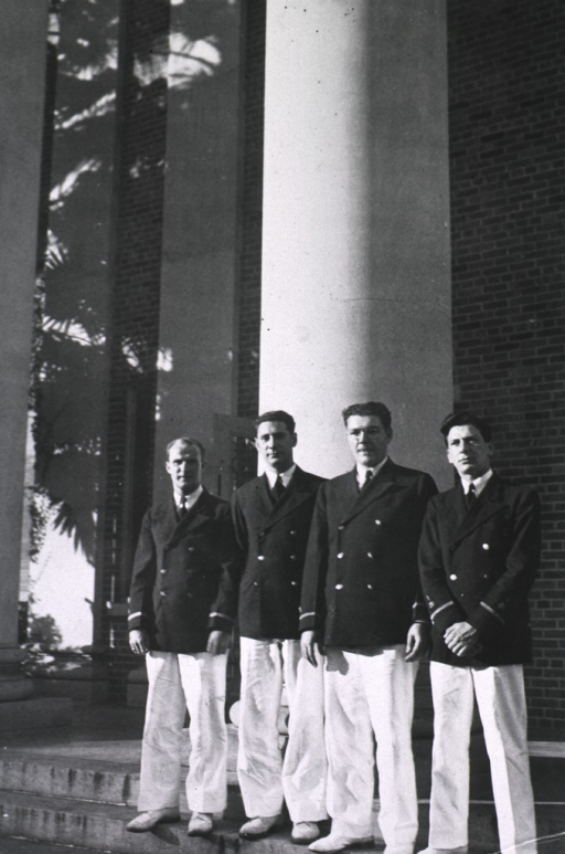 <p>Exterior view: four men wearing PHS uniforms stand on steps in front a pillar at the entrance to the hospital building.</p>
