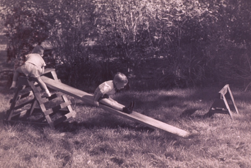 <p>Two children are playing on a wooden plank set on sawhorses.</p>
