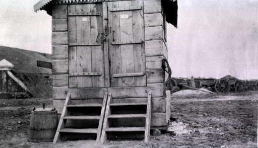 <p>A view of the front of a latrine with three steps leading up to the two doors.</p>