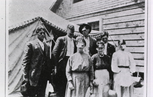 <p>Several patients, some wearing eye bandages, are standing in front of a tent, a wooden building is in the background.</p>