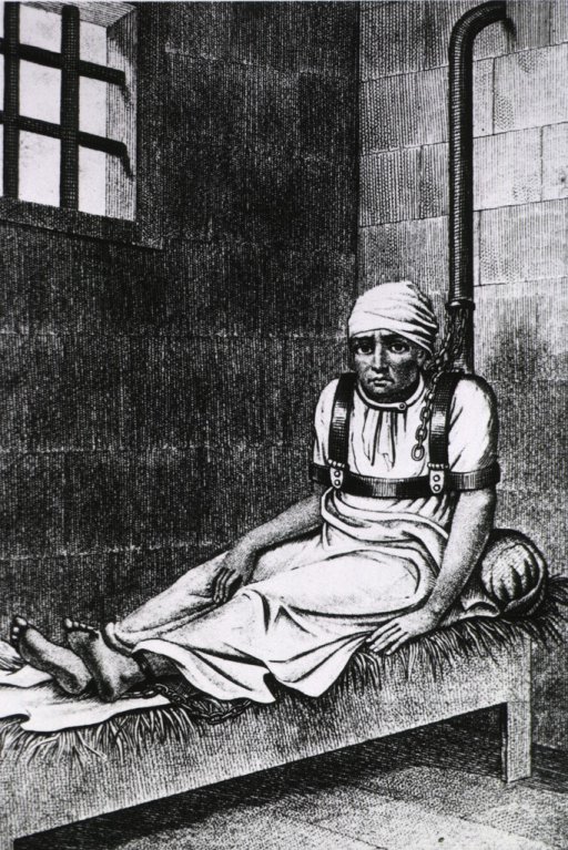 <p>A man is sitting on a straw bed in a prison; he is wearing a shoulder harness which is chained to the wall behind him; his feet are also shackled and chained to the wall.</p>