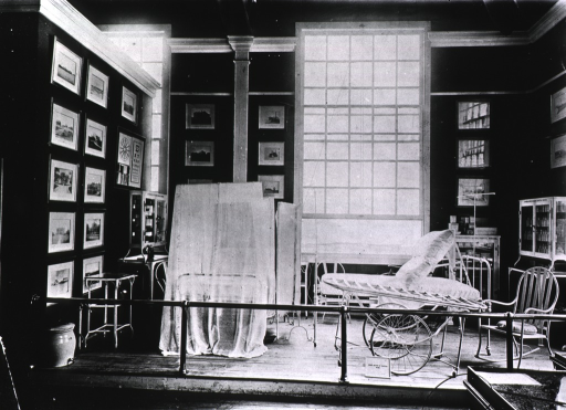 <p>View of a Jamestown Ter-centennial Exposition exhibit depicting a hospital room of the United States Public Health and Marine Hospital Service, furnished with a gurney, two beds (one covered in netting), chairs, and glass-fronted cabinets filled with medical supplies; probably part of the Army and Navy Exhibits in the Government Building, West.</p>